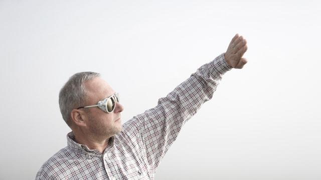 Heinz Graf hält die Hand gegen die Sonne und schaut in den Nebel am Flughafen Zürich.