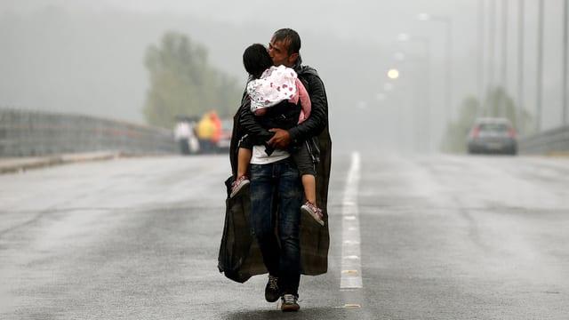 Ein Mann trägt im strömenden Regen sein Kind auf den Armen