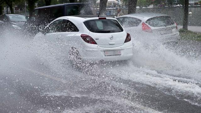 Autos fahren auf einer überfluteten Strasse im Tessin.
