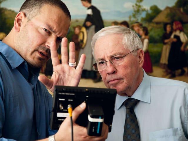 Bron und Blocher schauen auf einen Bildschirm. Im Hintergrund ein Anker-Gemälde.