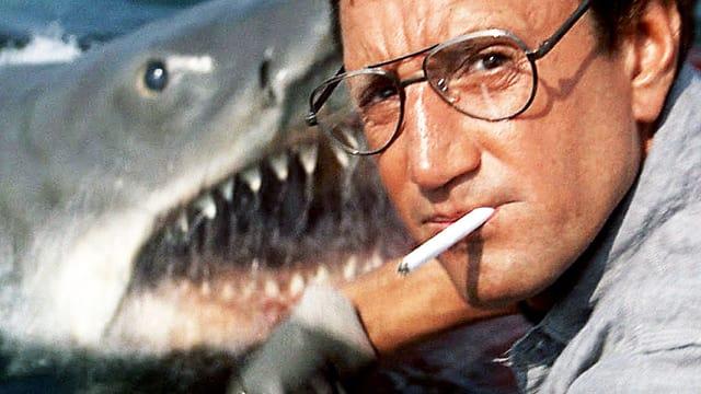 Mann mit Zigarett im Mund schaut in die Kamera. Hinter ihm taucht ein Hai auf.
