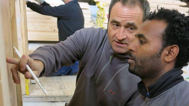 Zwei Männer schauen auf ein Brett, der eine erklärt etwas.