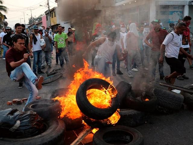 Brennende Autoreifen, Demonstranten.