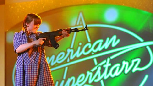 Mädchen in Kleid mit Machinengewehr vor Logo von American Superstar