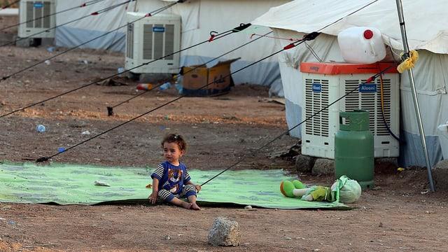 Kind sitzt vor Zelt.