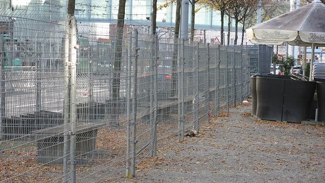Zwei Reihen mit zwei Meter hohen Maschendrahtzäunen stehen vor dem MUBA Gebäude.
