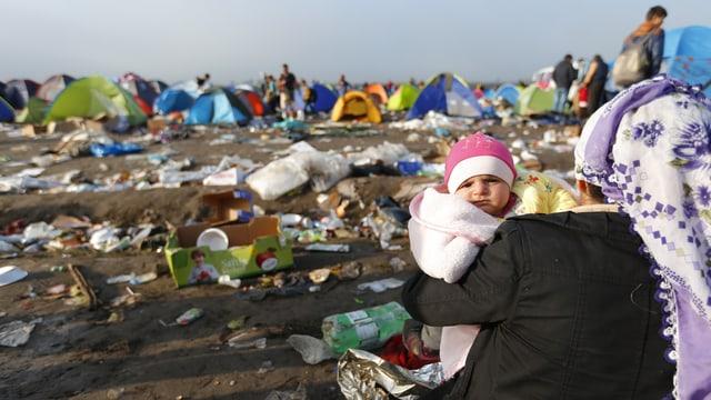 Mutter mit Baby schaut auf eine Zeltstadt