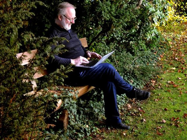 Ein Mann in dunkler Kleidung sitzt mit einem Laptop auf den Knien auf einer Holzbank, leicht versteckt hinter ein paar Tannenbaumzweigen.