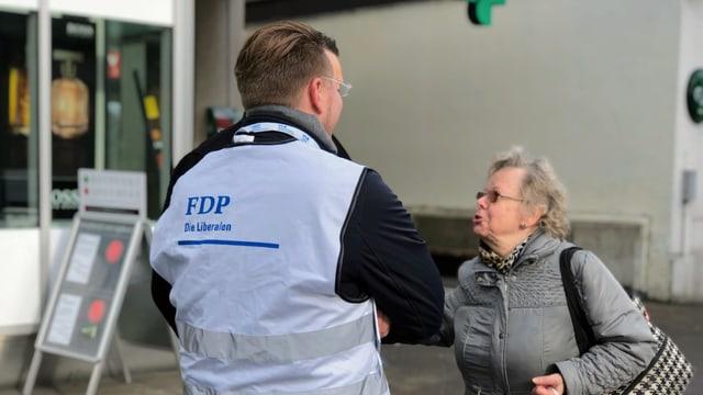 Ein Wahlkampfhelfer der FDP spricht mit einer älteren Frau.