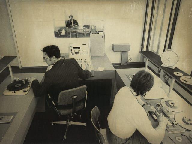 Ein Schwarzweissbild eines Radiostudios: Ein Mann und eine Frau sind an Tonbandmaschinen am Arbeiten.