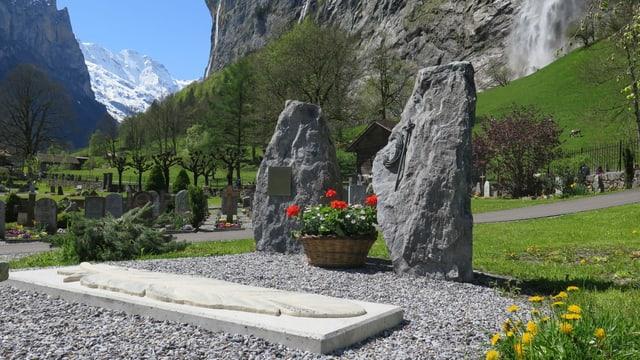 Zwei grosse Steine, eine Betonplatte mit eingravierter Feder, im Hintergrund Berge mit Schnee und ein Wasserfall