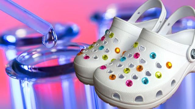 Weisse Clogs mit bunten Perlen, im Hintergrund sindLaborgefässe zu sehen