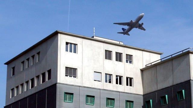 Ein Flugzeug fliegt über das Ausschaffungsgefängnis am Flughafen Zürich.