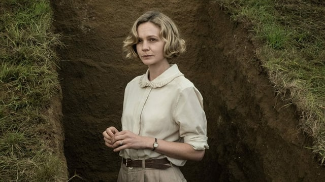 Eine junge, blonde Frau mit beigem Hemd und beiger Hose steht in einem Grab.