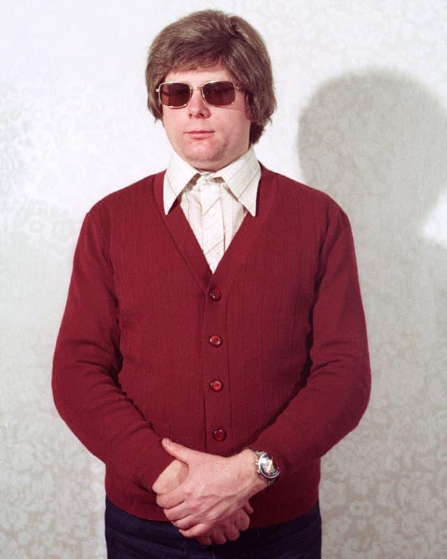 Ein Mann mit rotem Pullover, Perücke und Sonnenbrille.
