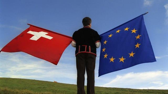 Maletg d'in svizzer che tegn la bandiera sivzra e quella da l'Uniun Europeica
