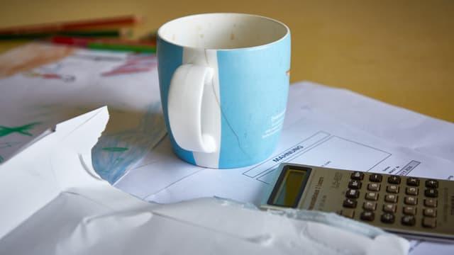 Tisch mit verschiedenen Rechnungen und Mahnungen, mit einer Tasse und einem Taschenrechner.