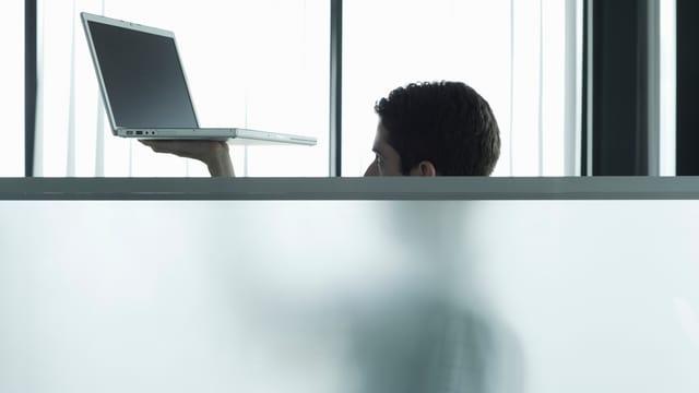 Ein Mann hält sein Laptop hoch hinter einer Milchglasscheibe, die ihn bis zur Nase verdeckt.