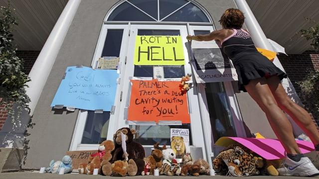 Plakate vor der Arztpraxis der Jägers. Auf einem steht auf Englisch geschrieben: «Schmore in der Hölle».