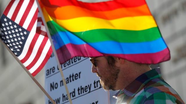 Ein Mann mit US- und Regenbogen-Fahne.
