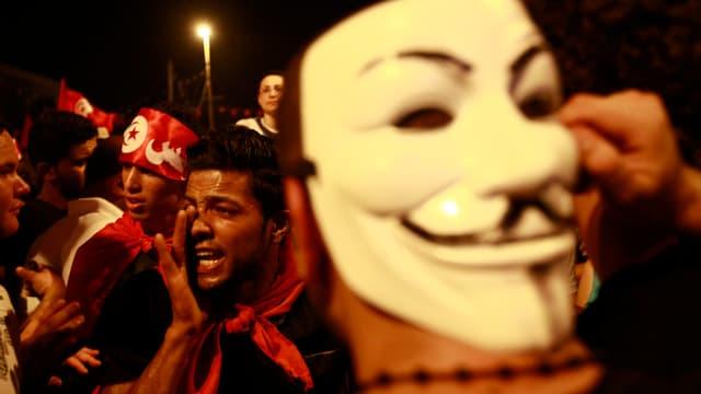 Demonstranten, im Vordergrund eine Maske