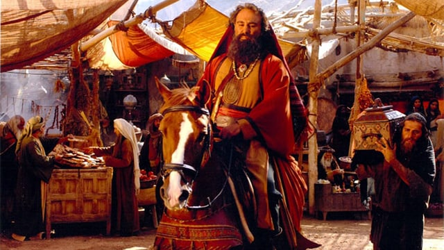 Filmszene: Ein Mann mit Bart reitet auf einem Pferd durch einen Markt.