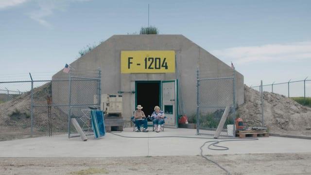 Ein Bunker vor dem ein Mann und eine Frau auf Campingstühlen sitzen.