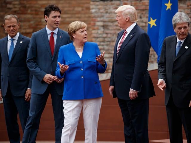 Politiker in einer Reihe stehend. Im Zentrum: Donald Trump.