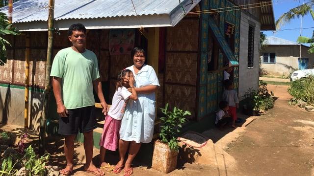Ein Mann, eine Frau und ein Kind vor einem Haus.