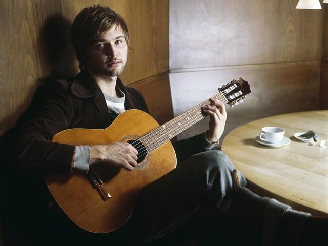 Portrait Nils Althaus mit Gitarre in einer Beiz an rundem Tisch.