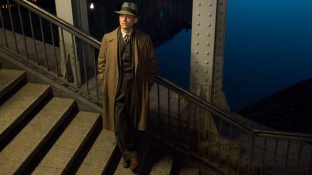 Protagonist der Serie steht nachdenklich auf einer Treppe.