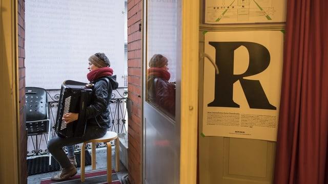 Das R-Logo der «Republik» an einer Türe angeheftet, dahinter spielt eine Frau Akkordeon.