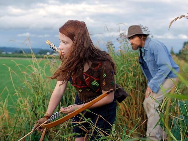 Eine junge Frau mit einem Pfeilbogen auf der Jagd, in ihrem Schlepptau ein Mann mit Jeanshemd und Hut.