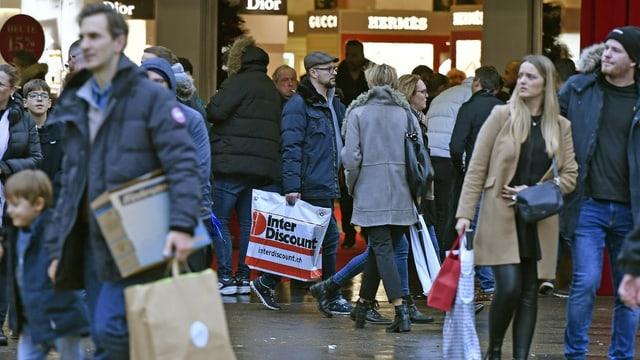 Menschen auf Einkaufsstrasse mit Taschen
