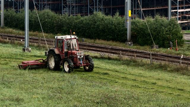 Ein Traktor auf einem Feld, dahinter Eisenbahnlinien.