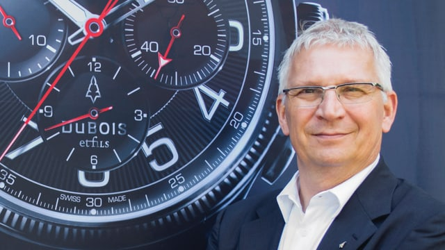 Thomas Steinemann steht vor einem Plakat mit einer Uhr.