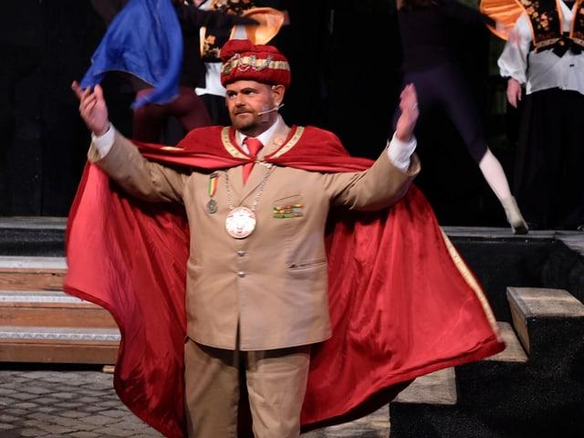 Ein Mann mit Turban und Umhang hält die Hände in die Luft.