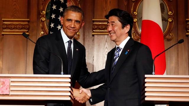 US-Präsident Obama und der japanische Premier Abe schütteln sich an einer Medienkonferenz die Hände.
