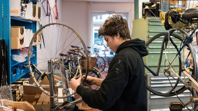 Ein Lehrling in einer Fahrrad-Werkstatt.