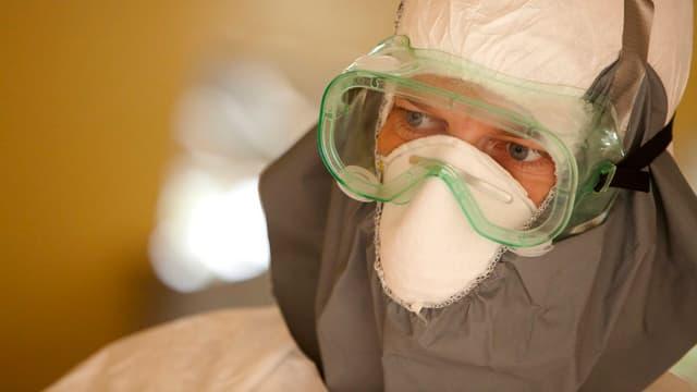 Mann in Schutzkleidung und Schutzbrille.
