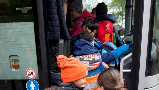 Kinder steigen in einen Bus ein.