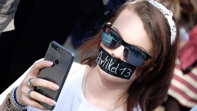 Junge Frau mit Kleber auf dem Mund. Darauf steht Artikel 13. Sie macht ein Selfie.