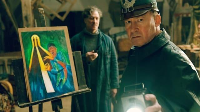 Filmstill: Ein Maler im Atelier, im Vordergrund ein Polizist mit Taschenlampe.