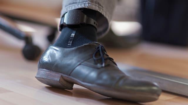 Herrenschuh unter Bürostuhl, Fussfessel am Bein