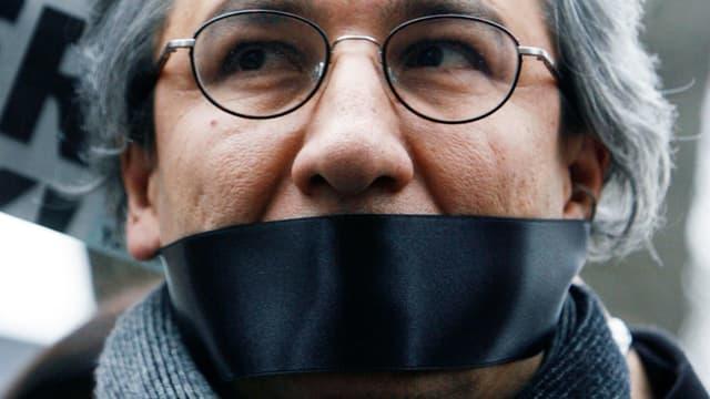 Ein Journalist mit Brille und bedecktem Mund.