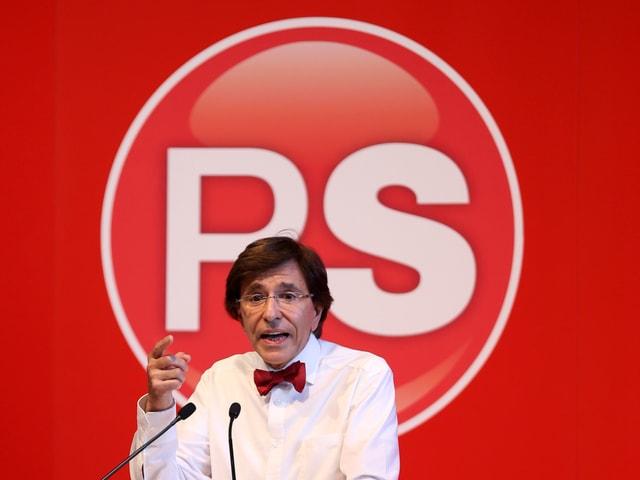 Elio di Rupo mit Fliege vor einer roten Wand mit dem Logo der Parti Socialiste.