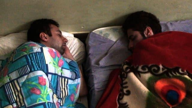 Zwei Männer schlafen, zugedeckt von bunten Decken