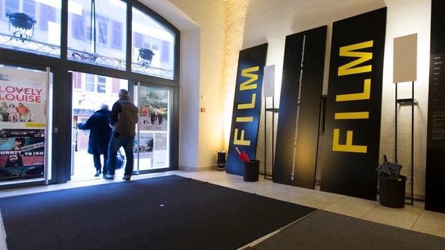 Kinofoyer mit zwei übergrossen Transparenten auf denen «Film» steht.