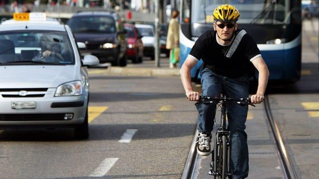 Ein Fahrradfahrer, auf dem Tramgleis in Zürich unterwegs