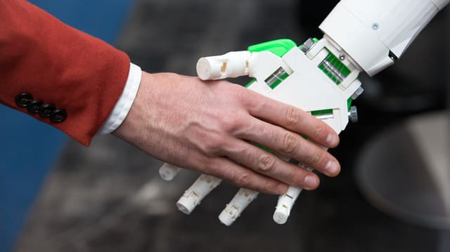 Menschliche Hand und Roboterhand.